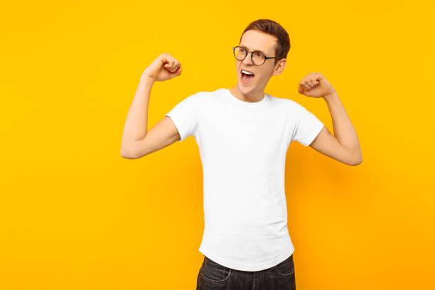 mann in gläsern, bekleidet mit einem weißen t-shirt, der mann, der gewann eine geste der sieg und erfolg auf einem gelben hintergrund zeigt - geek t shirts stock-fotos und bilder