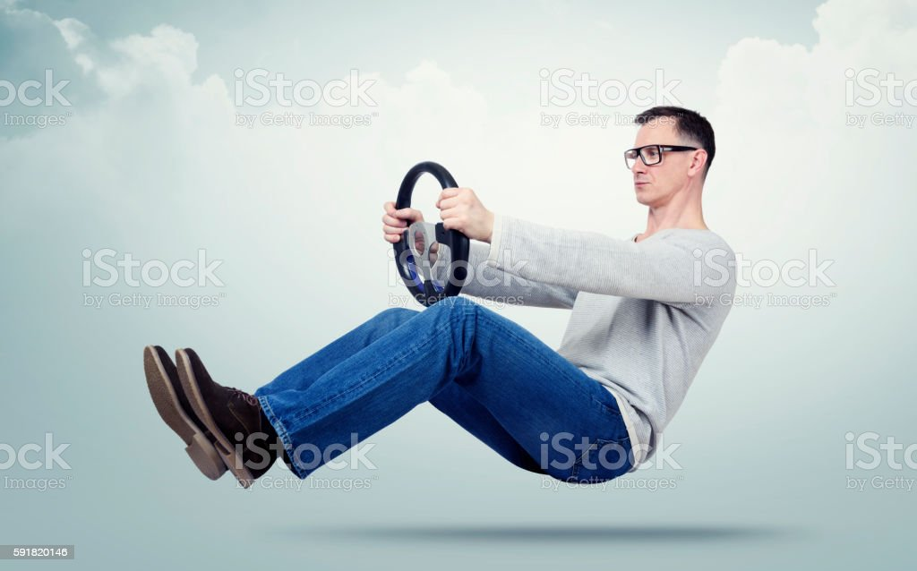Man in glasses drives a car with a steering wheel stock photo