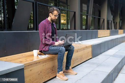 Man in glasses sitting on wooden bench and typing on laptop. Guy looking at screen. Notebooks and takeaway coffee near him. Building windows on background. Working outside and freelance concept