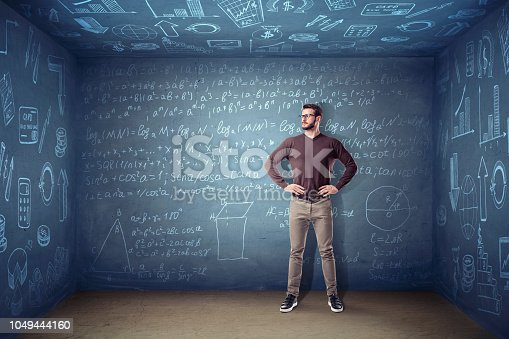 istock A man in glasses stands in a small square room where the walls are covered with chalk equations and graphs. 1049444160