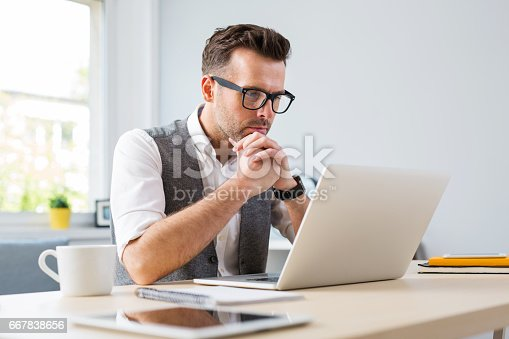istock Man in glasses working on laptop from home 667838656