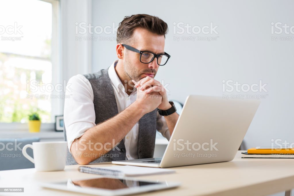 Man in glasses working on laptop from home stock photo
