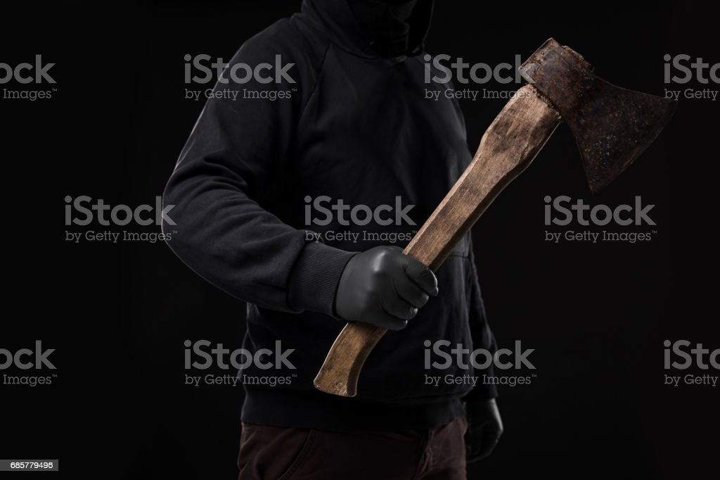 A man in gloves holds an ax in his hands against a black background royalty-free stock photo