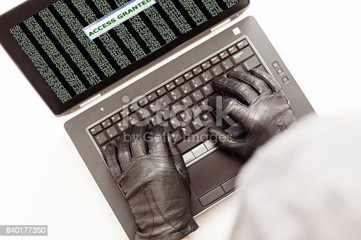 istock Man in gloves trying to hack computer network top View 840177350