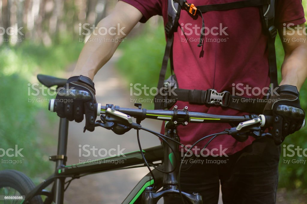 Man in gloves with the bike in the woods foto stock royalty-free