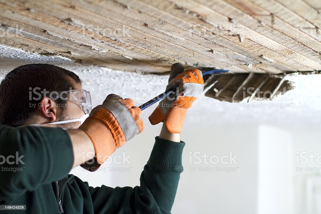 A man in goggles scrapes plaster off a ceiling royalty-free stock photo