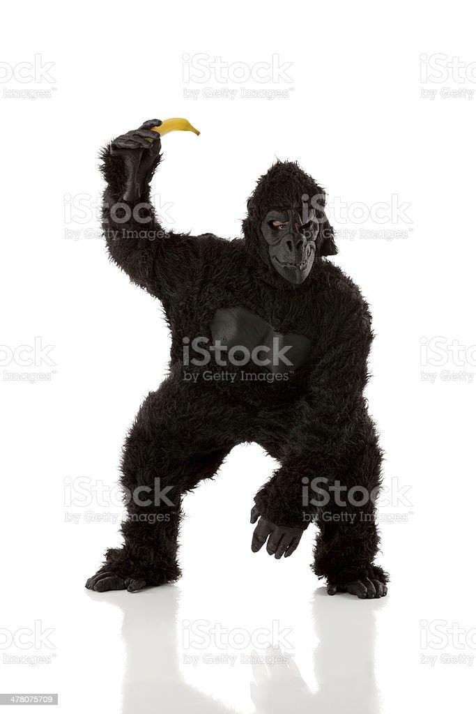 Man in gorilla costume holding banana royalty-free stock photo