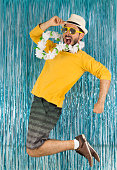 Bearded man in green and yellow clothes, sunglasses and Hawaiian necklace. Carnival of Brazil, eve of year end, euphoria and fun. Colorful and bright background.