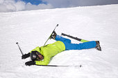 istock Man in green jacket lying on snow after skiing accident 164528991