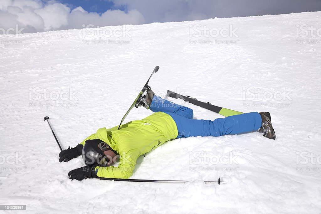 Man in green jacket lying on snow after skiing accident stock photo