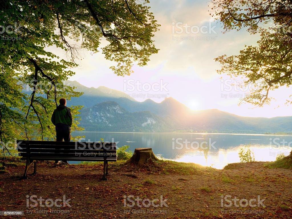 Man in green outdoor windcheater walk at lake bank. stock photo