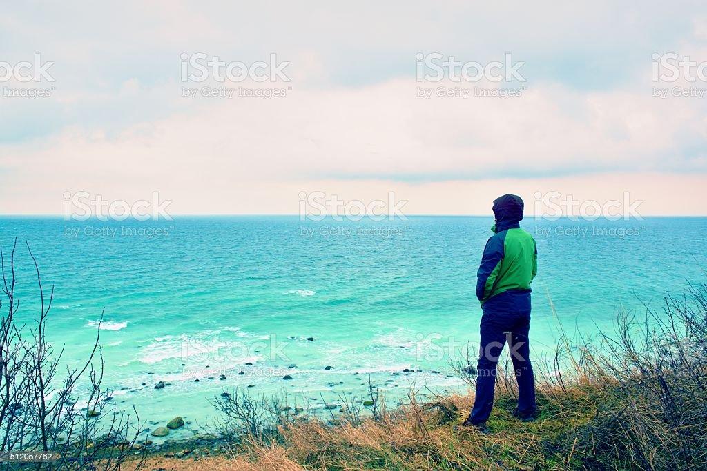 Man in green windcheater on cliff look at sea horizon. stock photo