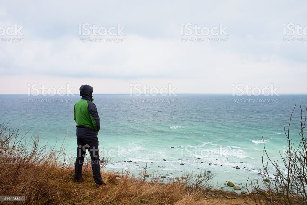Man in green windcheater stand on cliff above bay stock photo