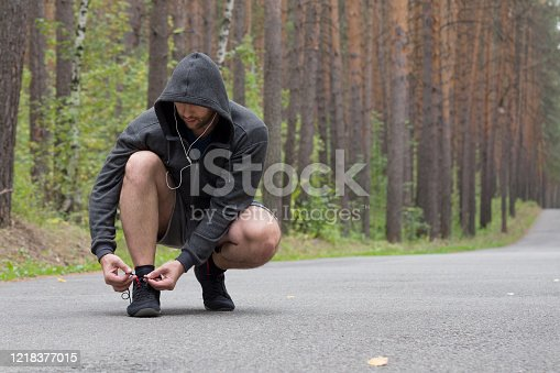 Man in grey hoodie tying sports shoes before going running and jogging on road in the forest, selective focus. Lifestyle, pause, activity, wellness, outdoor and fitness concept