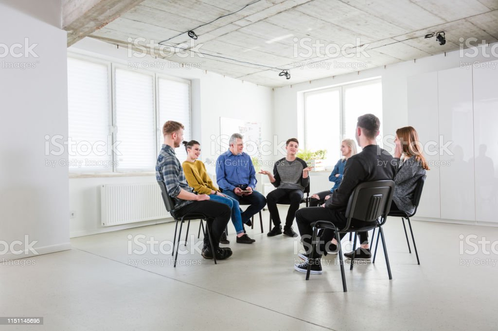 Man in group gesturing during therapy session Young man gesturing while talking during mental health therapy. University students are taking social worker's guidance in lecture hall. They are sitting in meeting. 18-19 Years Stock Photo