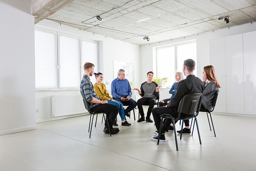 Man In Group Gesturing During Therapy Session Stock Photo - Download Image Now