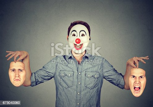 istock Man in happy clown mask holding two faces expressing anger and sadness 673040060