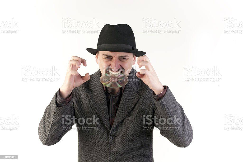 Man in hat biting a compact disc royalty-free stock photo