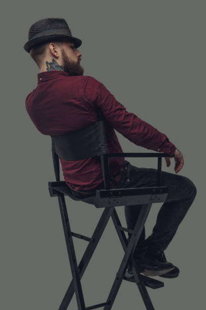 Man in hat sitting on film director's chair. stock photo