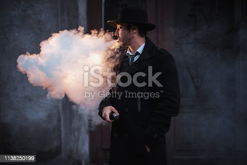 man in hat vaping electronic mod. man in classic hat and coat