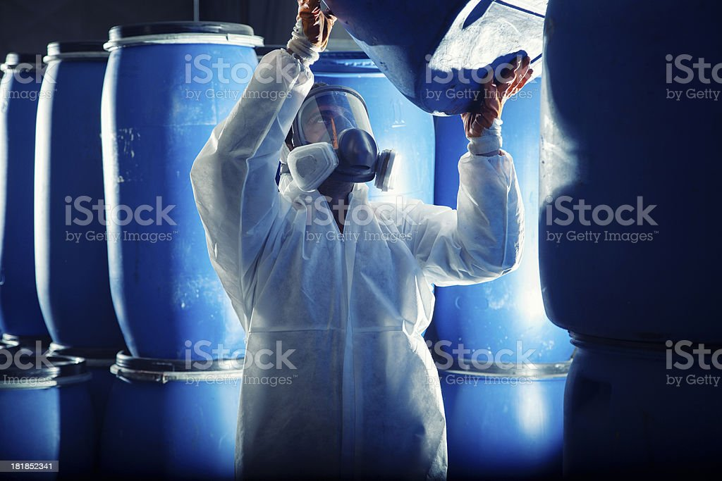 Man in hazmat suit and respirator lifting a blue barrel stock photo