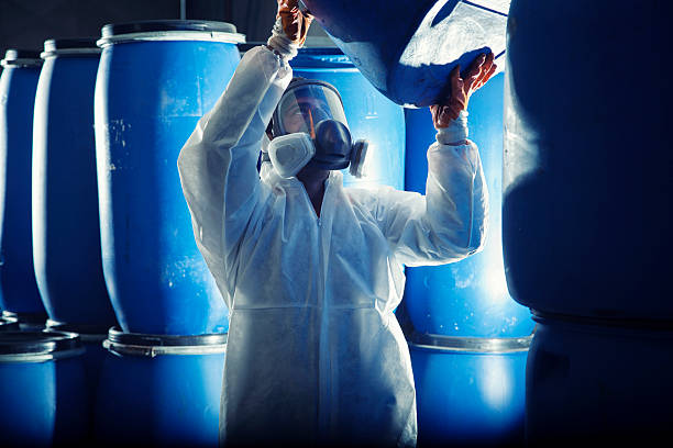 Man in hazmat suit and respirator lifting a blue barrel Chemical Barrels hazardous chemicals stock pictures, royalty-free photos & images