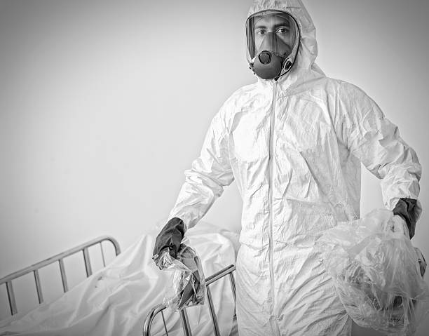 Man in Hazmat Suit Carries Contaminated Items in Plastic Bags stock photo