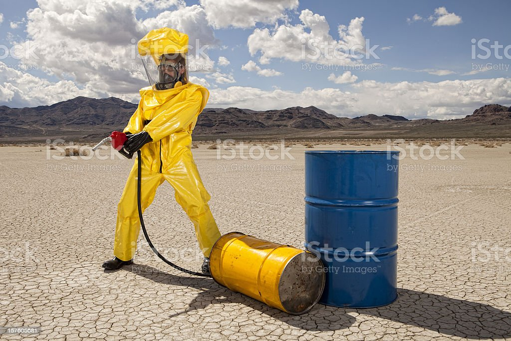 Man in hazmat suit causing an oil spill royalty-free stock photo