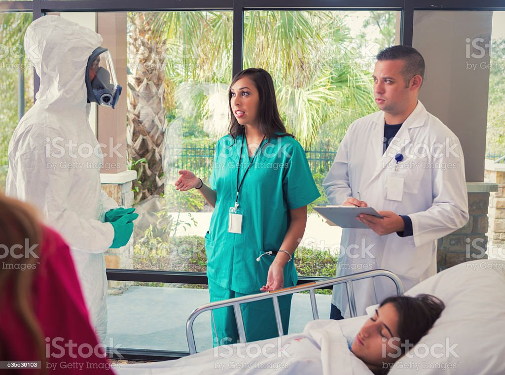 Man in hazmat suit quarantining contagious patient in hospital stock photo