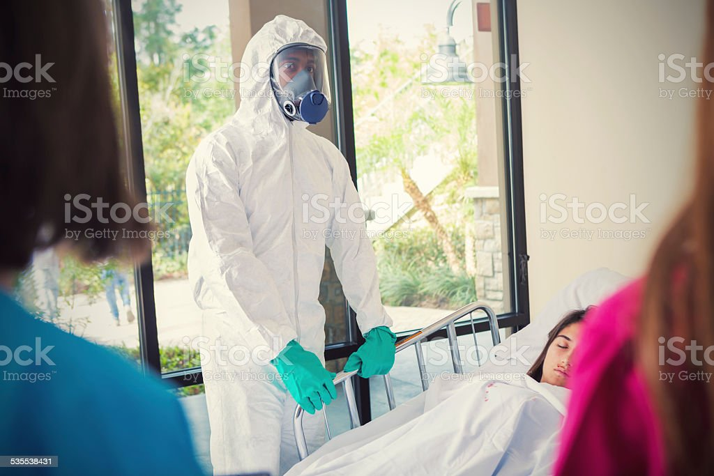 Man in hazmat suit treating contagious patient in hospital stock photo