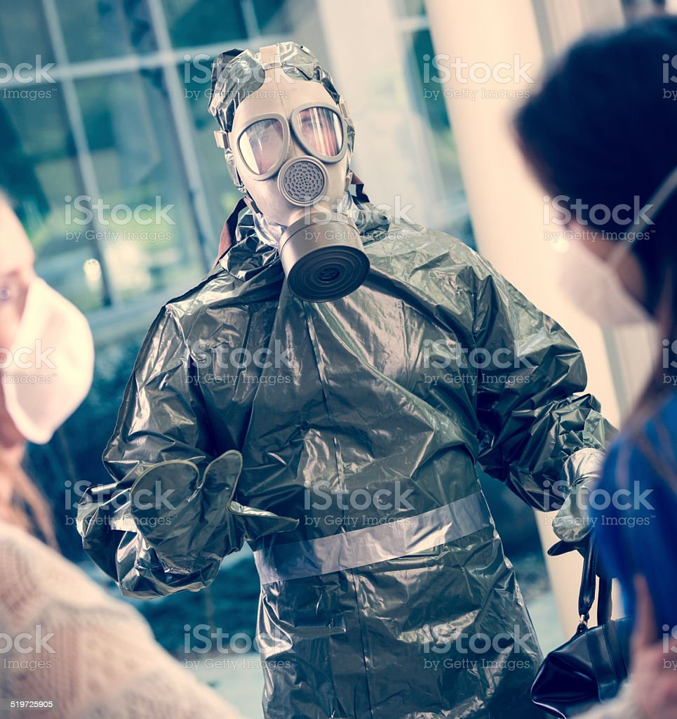 Man in hazmat suit trying to calm people during pandemic stock photo