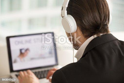 904263506 istock photo Man in headphones looking at laptop screen, back view. 843545420