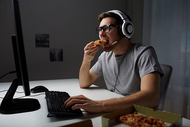 の男 ヘッドセットが自宅でコンピューターにビデオゲーム - ゲーム ヘッドフォン ストックフォトと画像