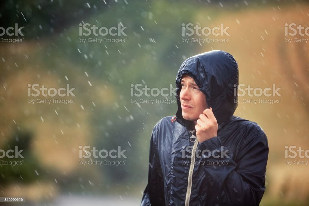Man in heavy rain stock photo