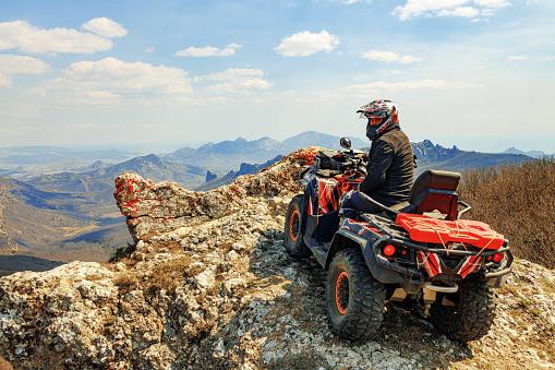 Man in helmet sitting on ATV quad bike in mountains on race