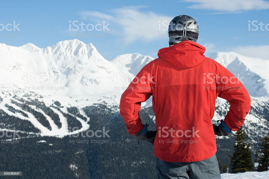 Man in helmet standing against snow-covered mountains, rear view stock photo