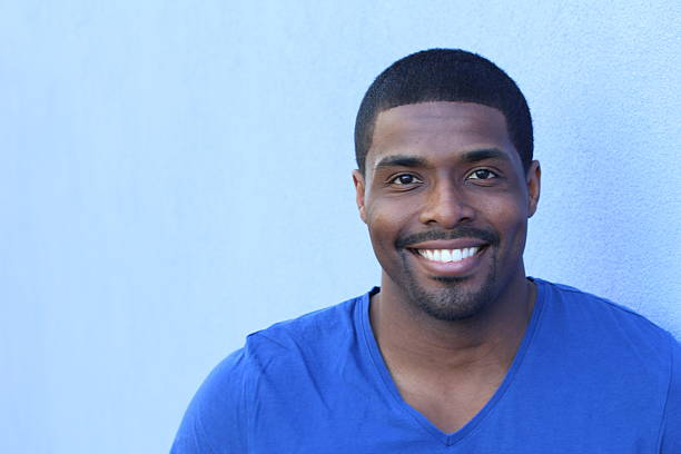Man in his 20s with a perfect smile Close up portrait of a happy black man in his 20s with a perfect smile isolated on a blue background with copy space. male animal stock pictures, royalty-free photos & images