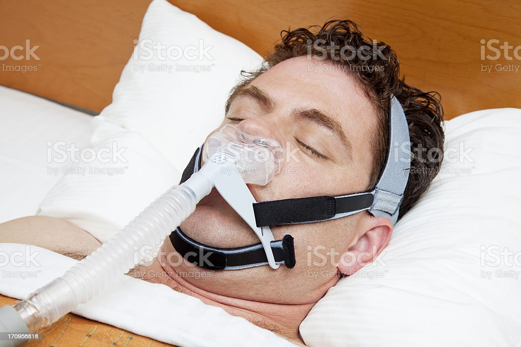 Man in his 30s with sleep apnea sleeping using CPAP royalty-free stock photo