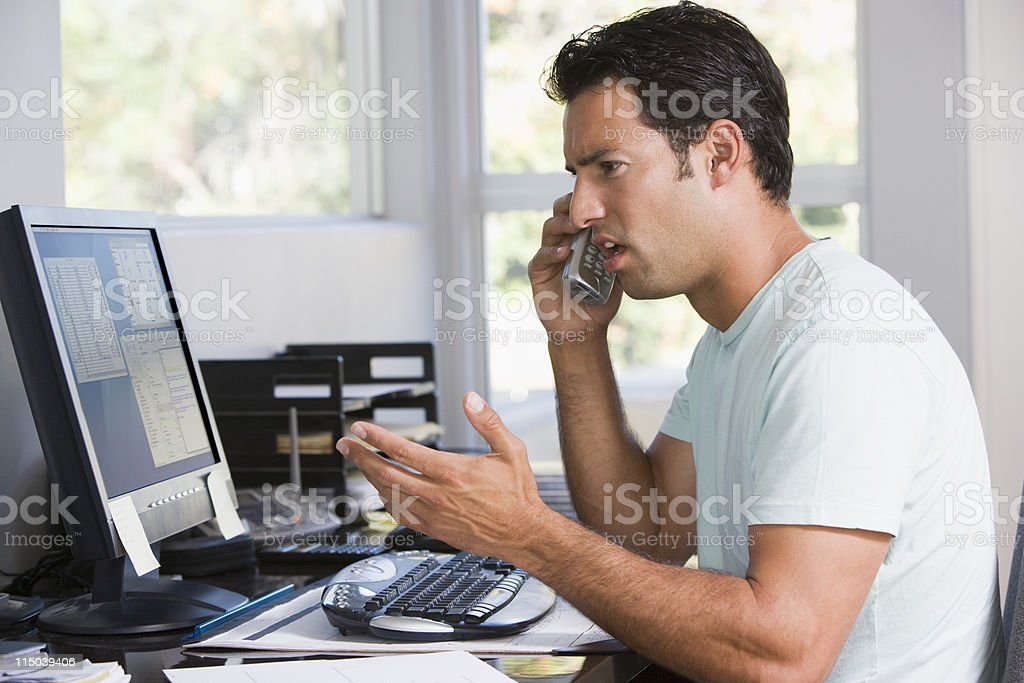 Man in home office on telephone using computer and frowning stock photo