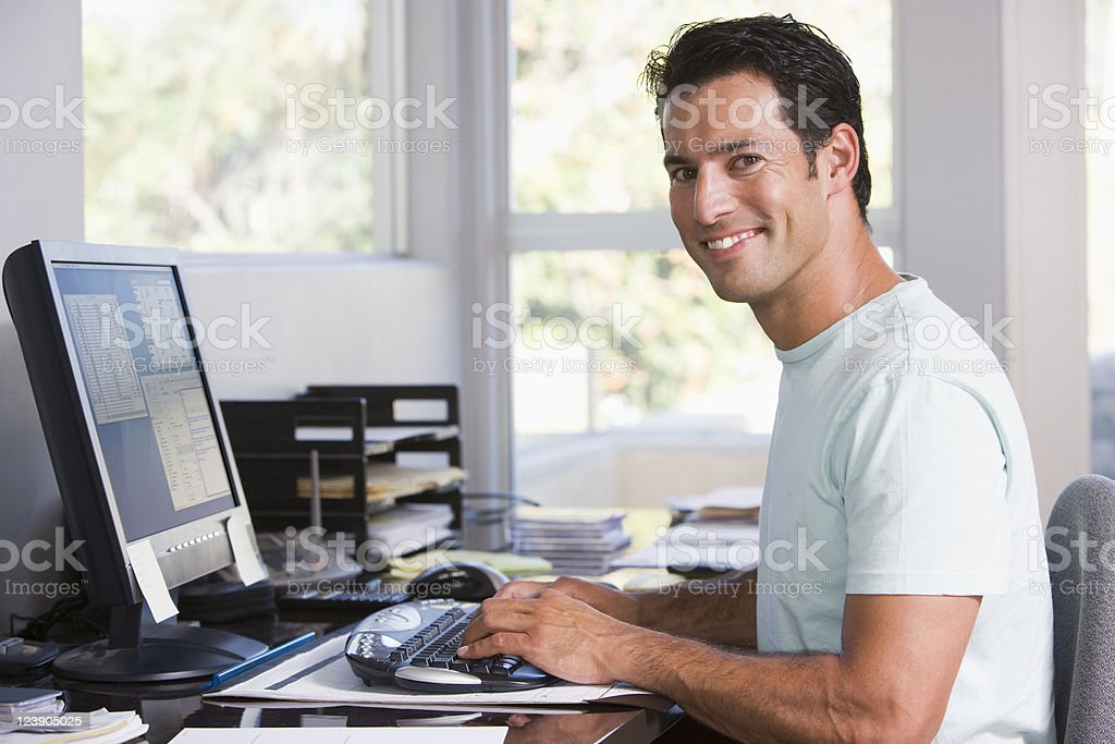 Man in home office using computer and smiling stock photo