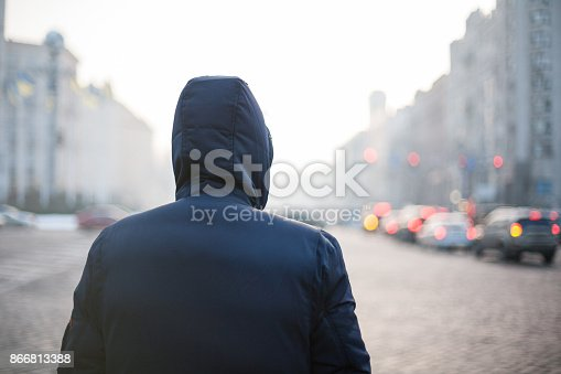 istock Man in hood walking through city street 866813388
