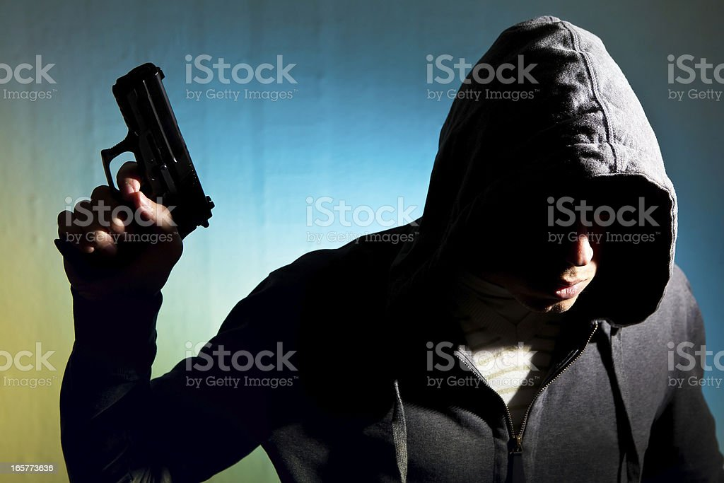 Man in hood with revolver royalty-free stock photo