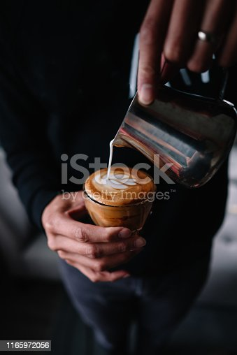 Taken at home, a man pours steamed milk into a cup of espresso to make cappuccino
