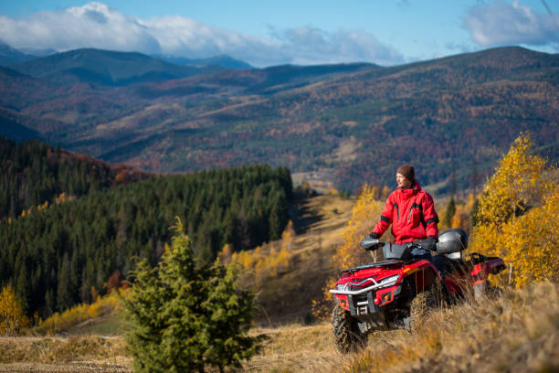 Man in jacket and hat riding on a red ATV on mountain roads on a sunny autumn day. Beautiful landscape of forest, mountains and blue sky with copy space Man in jacket and hat riding on a red ATV on mountain roads on a sunny autumn day. Beautiful landscape of forest, mountains and blue sky with copy space quadbike stock pictures, royalty-free photos & images