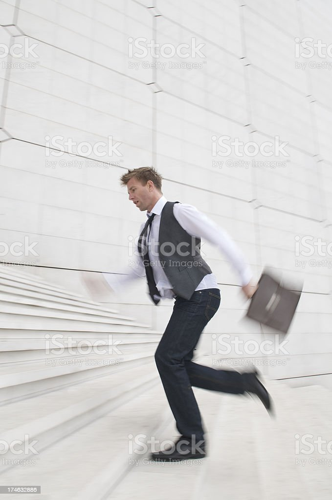 Man in Jeans and Black Tie Rushes Up White Steps royalty-free stock photo