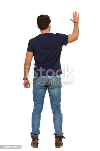 Man in jeans and blue t-shirt is standing with arm raised and waving hand. Rear view. Full length studio shot isolated on white.