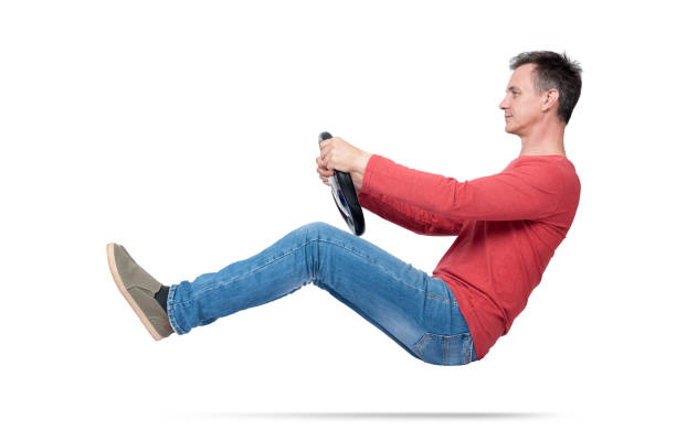 Man in jeans and red t-shirt drives a car with a steering wheel, isolated on white background. Auto driver concept Man in jeans and red t-shirt drives a car with a steering wheel, isolated on white background. Auto driver concept red shirt stock pictures, royalty-free photos & images