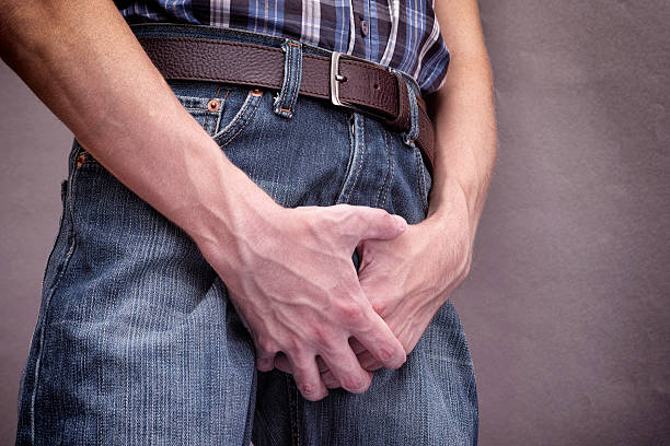 Man in jeans covers his crotch with hands stock photo