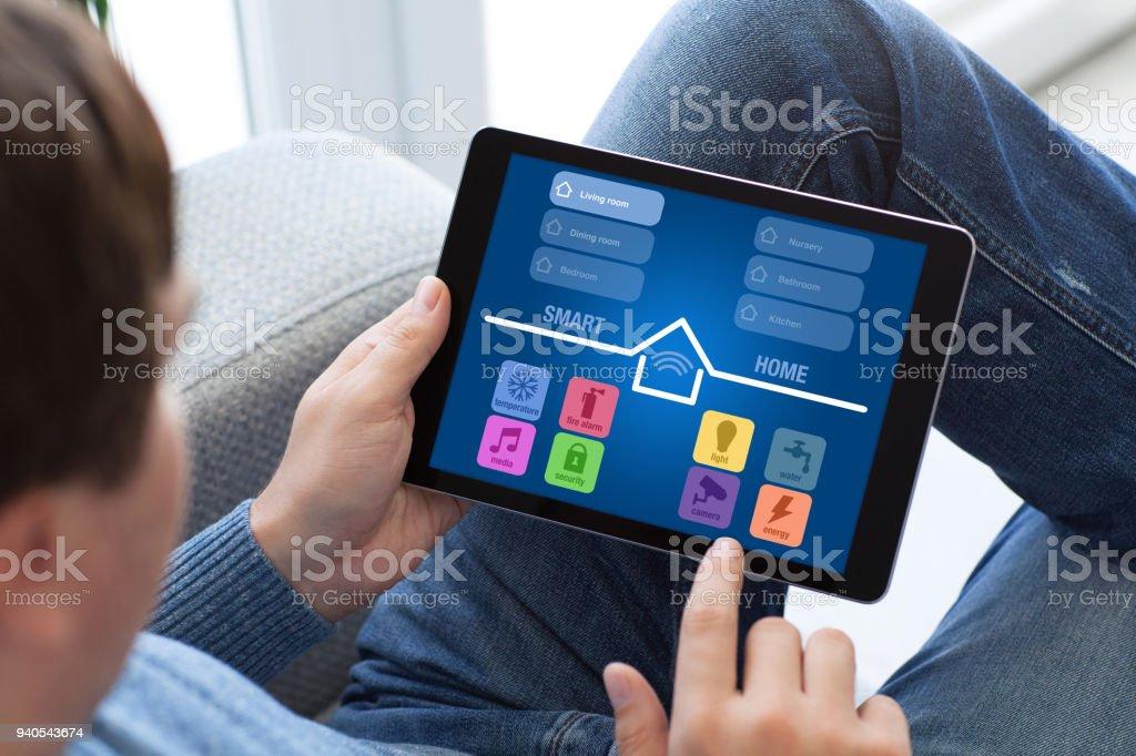 Mann in Jeans halten Tablet mit app smart home-Bildschirm – Foto
