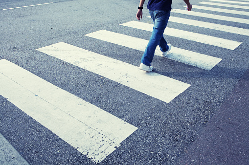 Man in jeans crossing the road.
